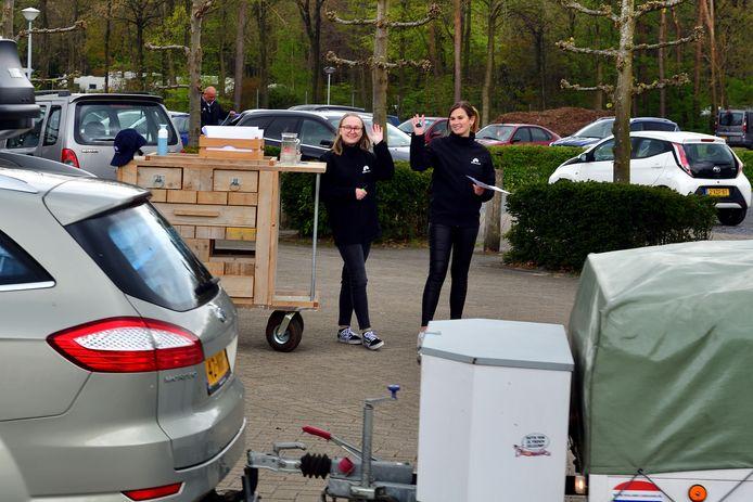 Stagiaire Nikki en medewerkster Melanie verwelkomen gasten met hun rijdende receptiekar.
