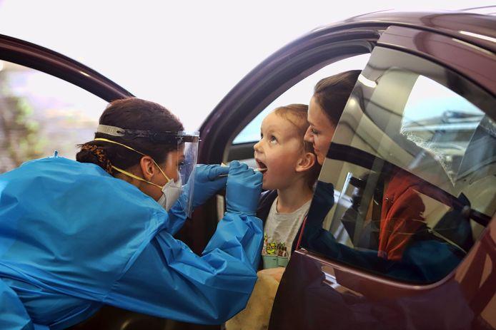 Een medewerker van de GGD doet een test bij een meisje op de testlocatie in Zuidland.