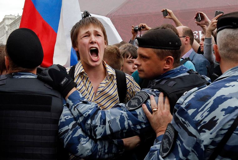 Een jonge demonstrant schreeuwt het uit, terwijl de politie hem tegenhoudt. Moskou, 12 juni. Beeld AP