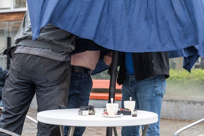 Regenweer... dan best een terrasje onder parasol. Als deze klanten hem open krijgen tenminste.