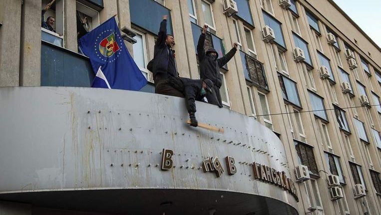 Pro-Russische demonstranten verwijderen het symbool van de staatsveiligheidsdienst in Loehansk. Beeld REUTERS