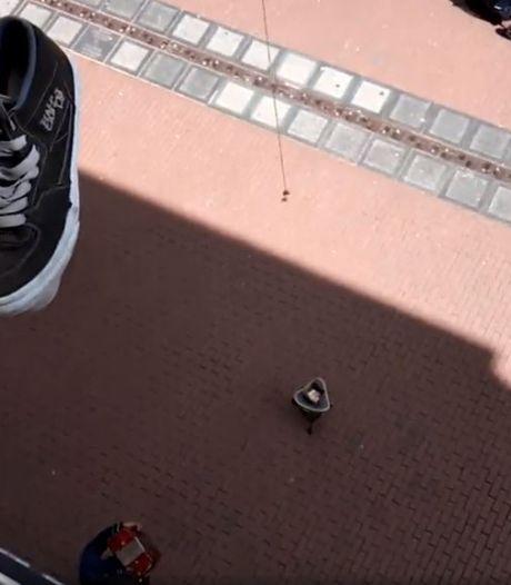 Jongens proberen met een magneet muntgeld te vissen van straatmuzikanten in Nijmegen
