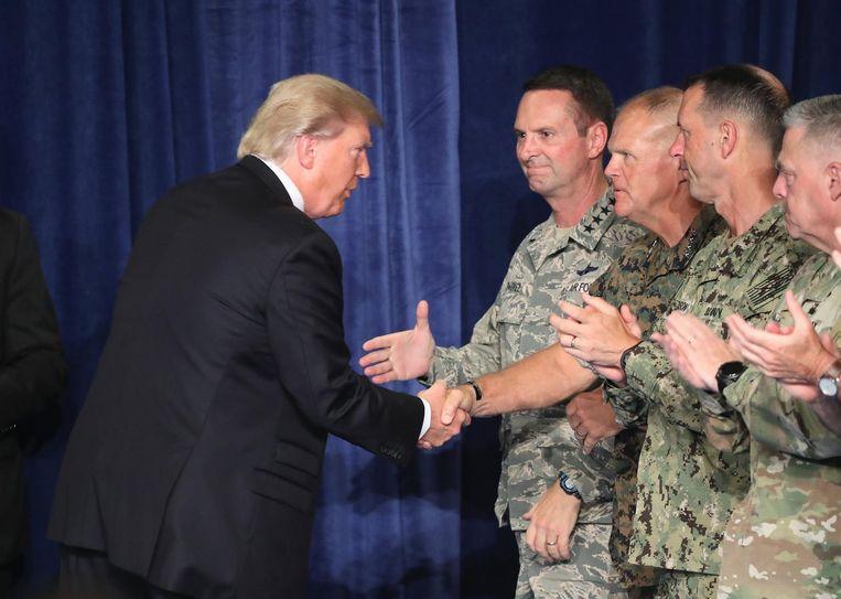 De Amerikaanse president Donald Trump groet militaire leiders voorafgaand aan zijn speech. Beeld ANP