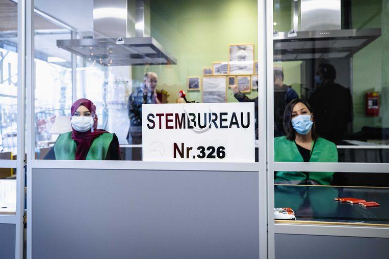 Medewerkers in een model-stembureau in Rotterdam Charlois. Voor de Tweede Kamerverkiezingen moeten alle stembureaus coronaproof worden ingericht. Beeld ANP