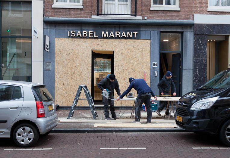 Op de stoep voor boetiek Isabel Marant staan drie vrolijke Poolse mannen hout te zagen. Beeld Nina Schollaardt