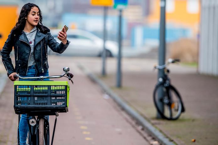 Een meisje gebruikt haar telefoon tijdens het fietsen.