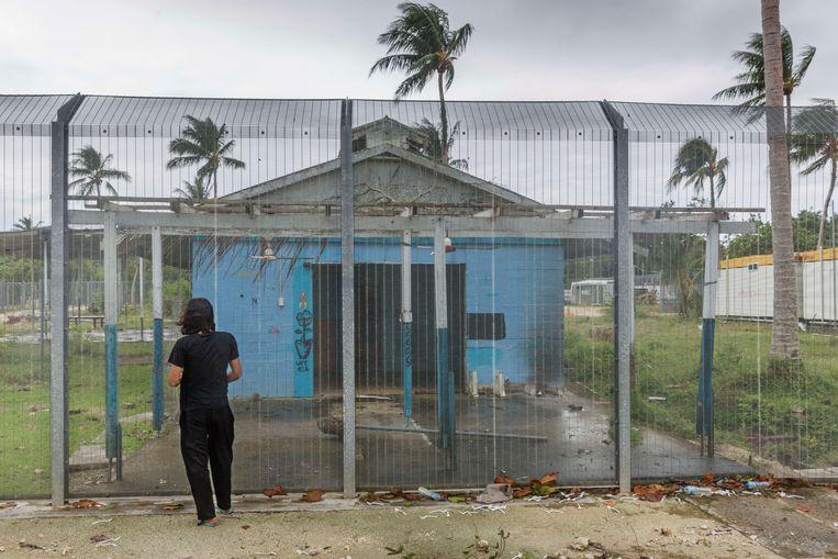 Behrouz Boochani bij het gebouw op Manus waar hij jaren verbleef. 'Vierhonderd verwaarloosde mensen in een gloeiend hete, smerige kooi', zo schreef hij daarover.   Beeld LightRocket via Getty Images