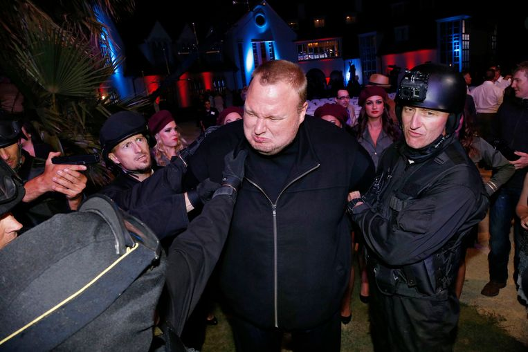 Actors in police costume mock-arrest Megaupload founder Kim Dotcom (C), as he launches his new file sharing site