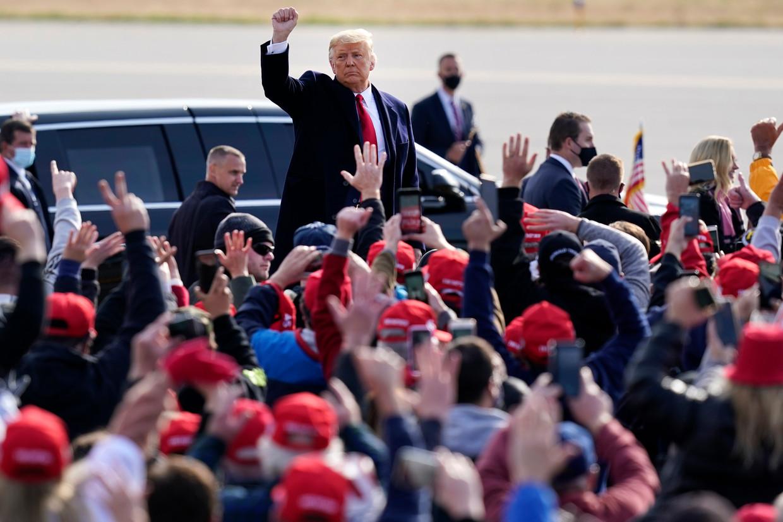 President Donald Trump steekt een vuist op naar zijn supporters tijdens een campagnestop in Londonderry, New Hampshire.  Beeld AP
