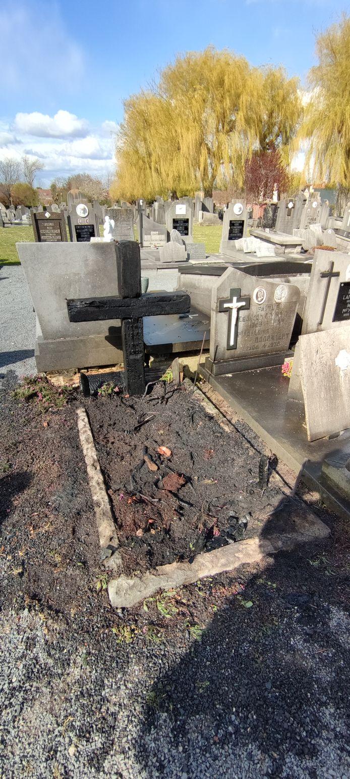 Een houten kruis en grafzerk vatten vuur.