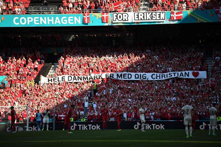 Spelers en toeschouwers applaudisseren in de tiende minuut voor Christian Eriksen. Op het spandoek staat: 'Heel Denemarken is bij je, Christian'. Beeld AFP