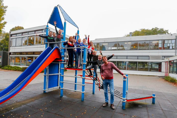 Directeur René Rooijakkers met kinderen die hopen dat het speeltoestel ook bij de nieuwe school een plekje krijgt.