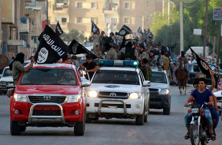 Islamitische strijders rijden triomfantelijk door de straten van Raqqa, nadat daar op 30 juni 2014 het kalifaat van IS was uitgeroepen. Beeld REUTERS