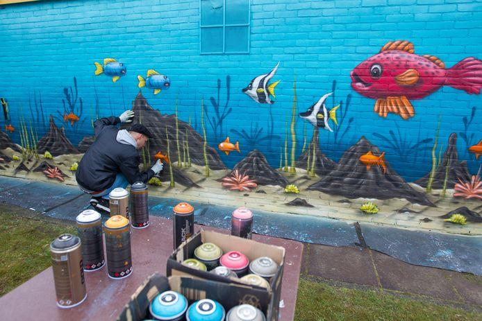 Bij zwembad De Dolfijn in Best maakt kunstenaar Finn Zweemer zijn nieuwe muurschilderingen.