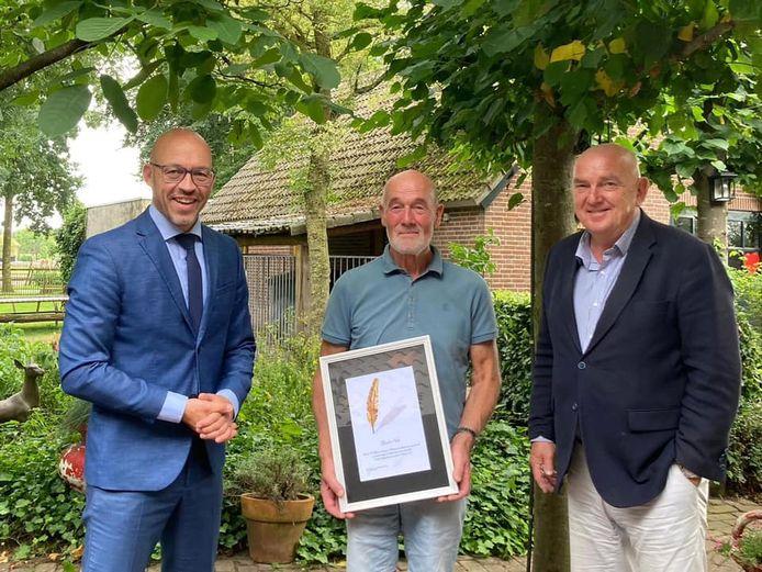Burgemeester Han Looijen (links) en wethouder Eric van den Dungen (rechts) van de gemeente Sint-Michielsgestel overhandigden paardenfokker Willie Wijnen uit Berlicum de gouden veer.