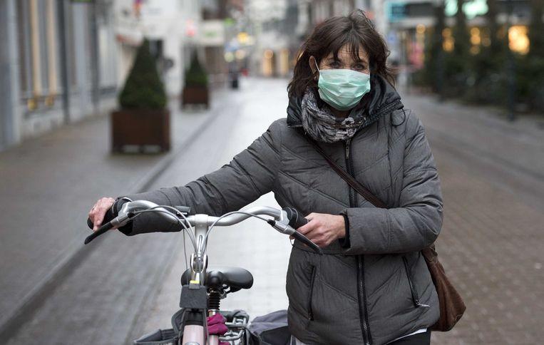 2014-12-17 00:00:00 ROERMOND - Een fietser met mondkapje loopt in het centrum van de stad dat deels is afgesloten omdat er asbest is vrijgekomen bij een brand. ANP MARCEL VAN HOORN Beeld ANP