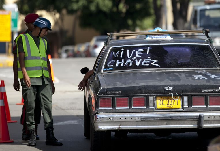 Een taxi wordt aangehouden bij de ingang van het ziekenhuis waarin president Hugo Chavez is opgenomen. Op de achterruit staat: Leve Chavez. Beeld ap