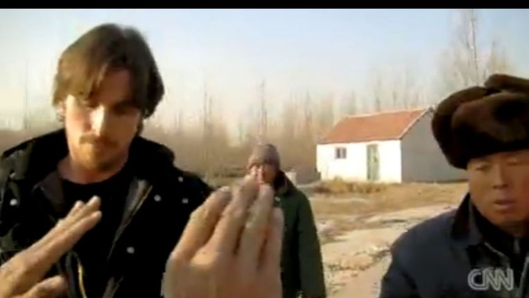 Christian Bale wordt door Chinese bewakers de toegang ontzegd. (Still) Beeld