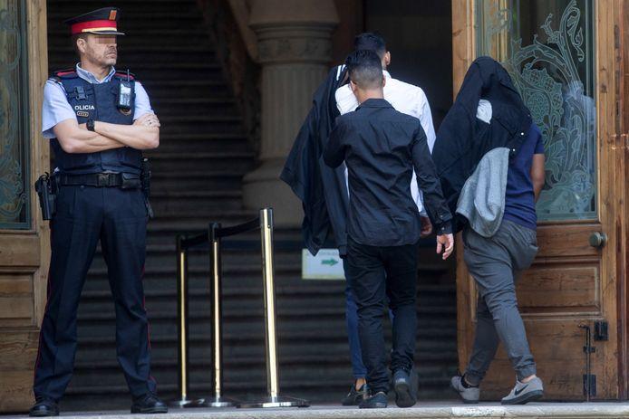 Drie van de beklaagden komen aan in de rechtbank.