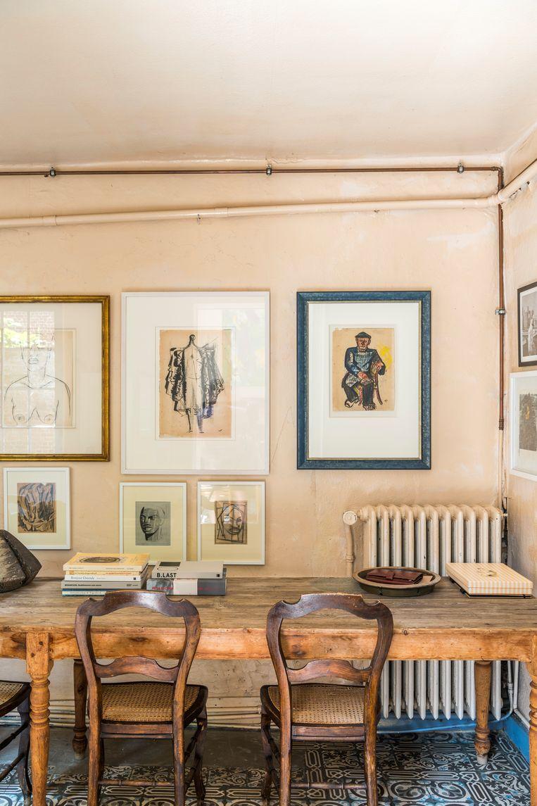 Aan de muur tegen de lange eettafel: een collage met werken van Karel Maes, Mark Macken en Jules De Sutter. Beeld Luc Roymans