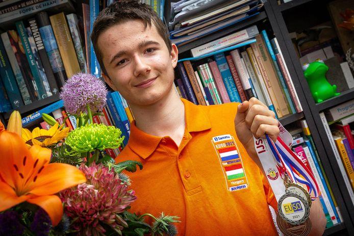 Revi Gerner met de bos bloemen die hij van zijn school, het Tromp Meesters in Steenwijk, heeft gekregen. De medailles zijn van vorige olympiades: vanwege de online olympiade heeft hij geen medaille uit Boedapest gekregen.