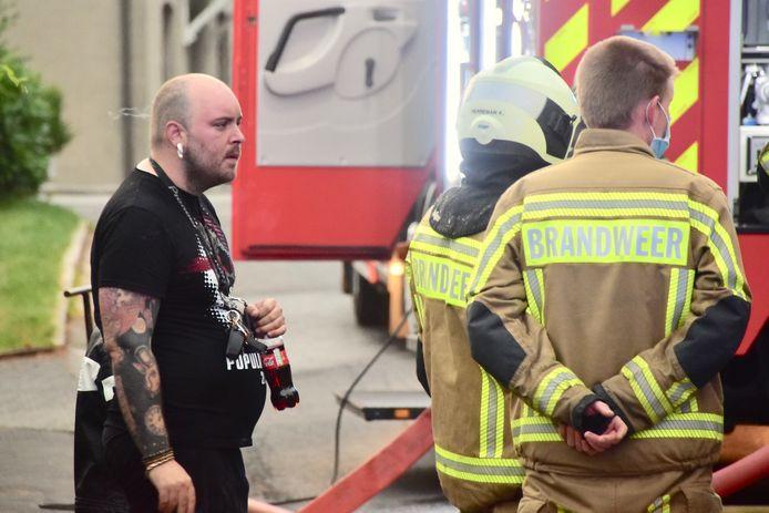 Bewoner Frederik Dooms (33) in gesprek met de brandweer, na de bluswerken in zijn woning op Walbrugge in Tiegem.
