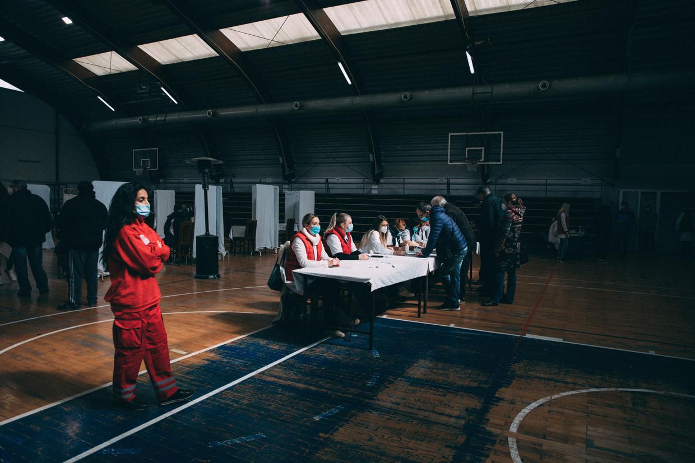 Bij binnenkomst in de sporthal in Kragujevac vindt eerst de registratie plaats, daarna volgen een gesprek met een arts (linksachter op de foto) en de prik. Beeld Marlena Waldthausen