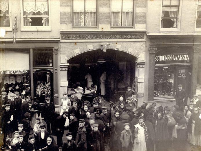 Een groep bedelaars op de wekelijkse bedeldag op vrijdag voor vleeschhouwerij G. Molsbergen aan de Lange Viestraat. De foto is gemaakt in 1905.