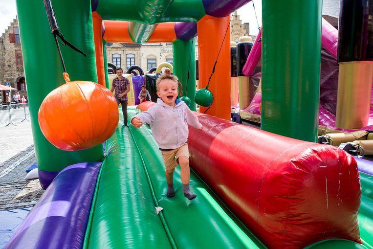 Een jongetje baant zich vol enthousiasme een weg door het opblaasbare hindernissenparcours op de Grote Markt.