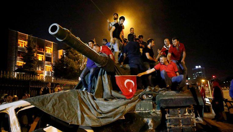 Aanhangers van president Erdogan hebben in Ankara bezit genomen van een tank. Beeld reuters