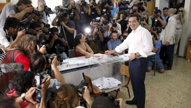 Tsipras laat zich fotograferen terwijl hij stemt in Athene. Dat doet de premier met de glimlach. Beeld © REUTERS