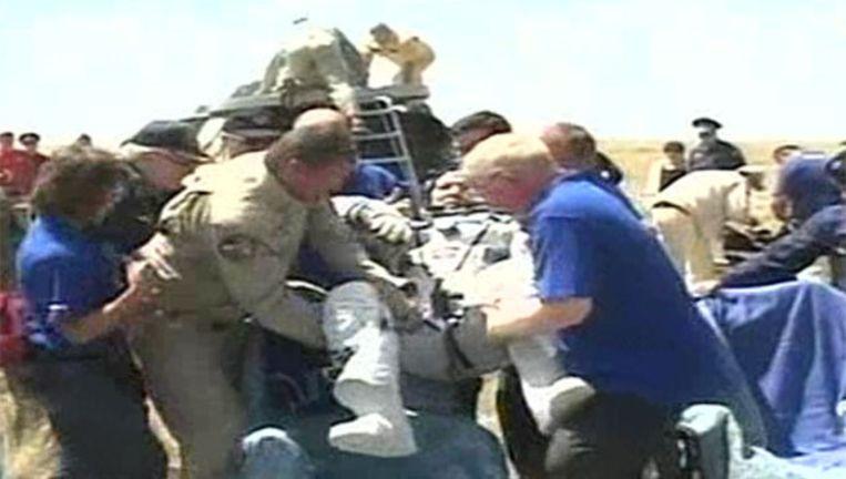 Commandant Oleg Kononenko wordt als eerste uit de capsule gehesen. Beeld