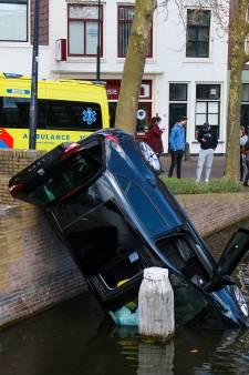Merkwaardig ongeluk: auto rijdt van kademuur en belandt half in het water in Gouda