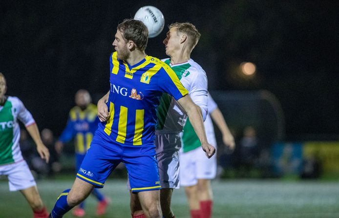 Veenendaal-speler Gert Jan Snijders (voorgrond) vecht een duel uit met zijn tegenstander van EDO.
