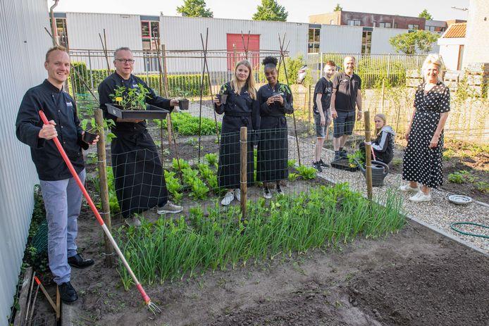 Docenten en leerlingen in de moestuin van MaxX Onderwijs in Neede. vanaf links: Michiel, Erwin, Elle, Jurninneisis, Nick, Habib, Storm en Yvonne.