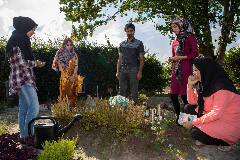 Moeder Delmira (r) en vader Akbar, met hun drie dochters Maedeh, Sogand en Kosar bij het graf van Meesam.  Beeld Negin Zendegani