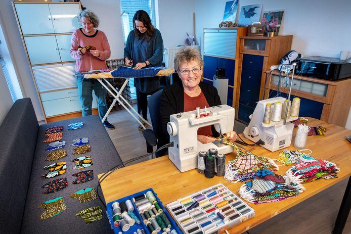 Betty Verbree achter de naaimachine met achter haar dochter Louise (l) en schoondochter Lotje.