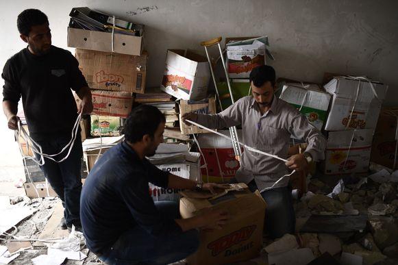 Vrijwilligers verzamelen documenten tussen het puin van de universiteit van Mosoel.