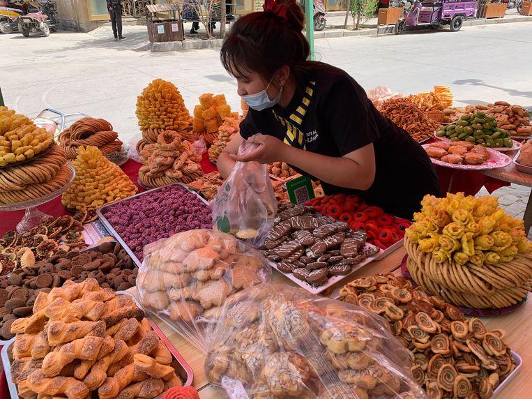Op de markt in Yarkant verkoopt een vrouw lekkernijen voor de iftar.  Beeld Eefje Rammeloo
