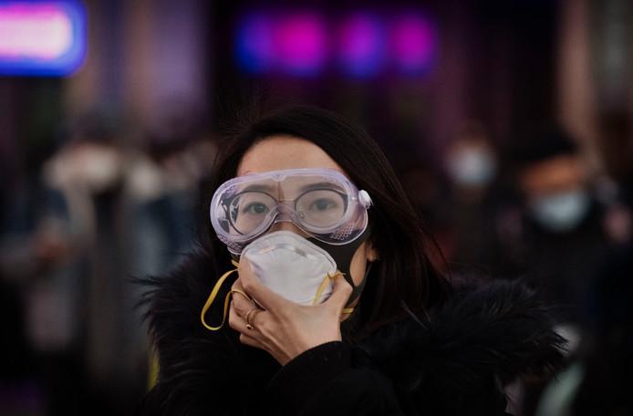 Een Chinese vrouw draagt ter bescherming een veiligheidsbril en een mondkapje.