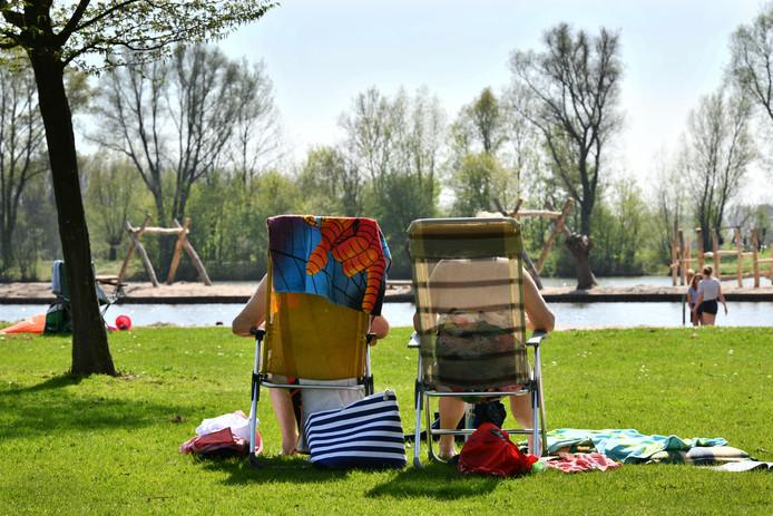 Bezoekers genieten van de zon bij recreatiegebied De Meent in Beusichem. Op de achtergrond is het speeleiland voor kinderen te zien.