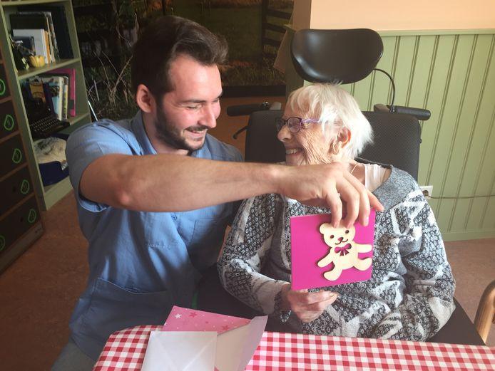 Mevrouw Maasmans is blij met de post die zij dagelijks krijgt van kinderen. Verzorger Michel van der Ouderaa geniet mee in verpleeghuis Cederhof in Kapelle.