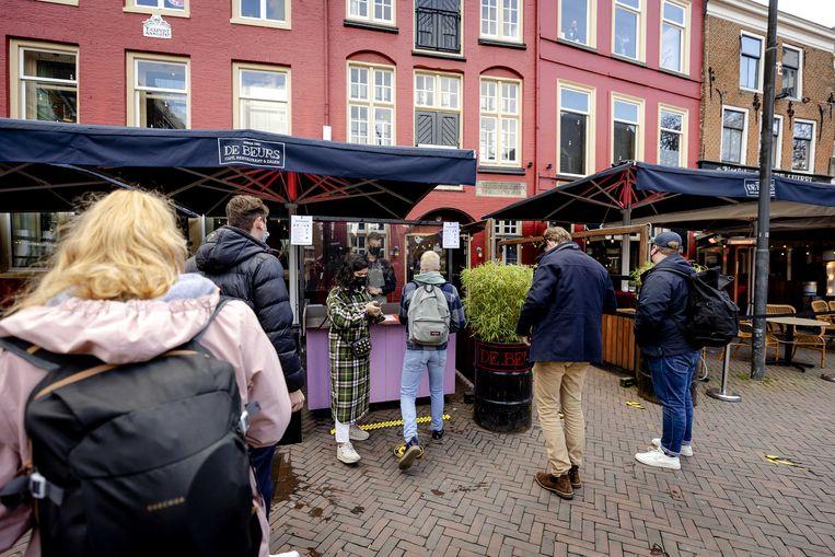 Bezoekers in de rij voor café De Beurs in Utrecht, in april van dit jaar, tijdens een proef met cafébezoek. Beeld ANP