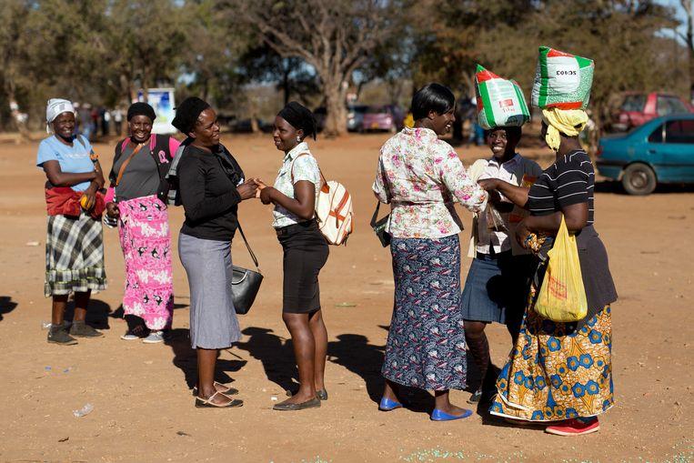 Zimbabwaanse vrouwen met voedsel dat is geschonken door de Zanu-PF, de partij van president Mnangagwa. Beeld AP
