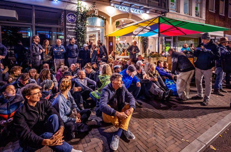 Maandagavond verzamelden zich enkele tientallen mensen bij het Utrechtse restaurant Waku Waku. Even daarvoor werd het op last van de gemeente gesloten omdat het geen QR-codes scande. Beeld Raymond Rutting / de Volkskrant