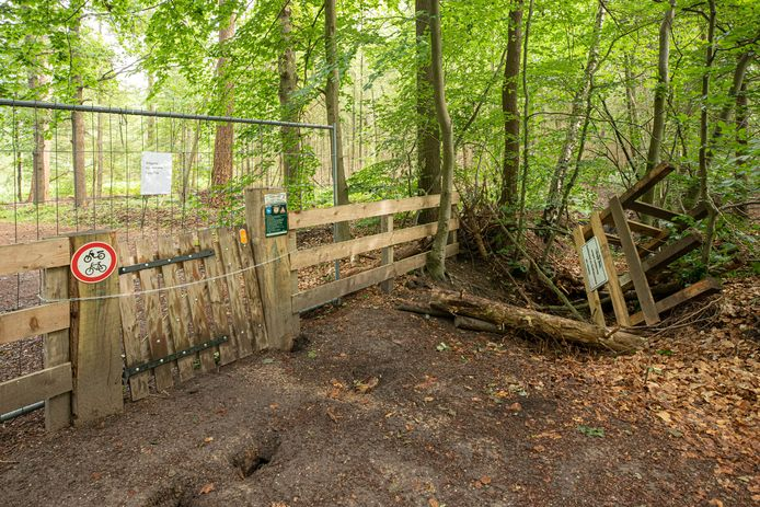 Het oorspronkelijke hekwerk is uit de grond gerukt en ligt rechts. Een bouwhek sluit het pad nu af.