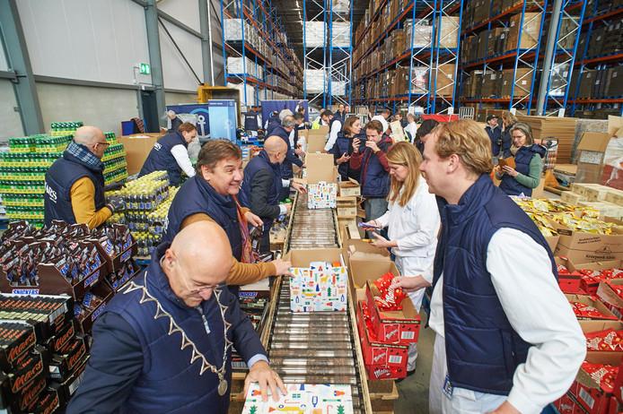 René Froger en burgemeester Kees van Rooij helpen mee met het inpakken van voedselpakketten in de loods van Kuehne + Nagel in Veghel.