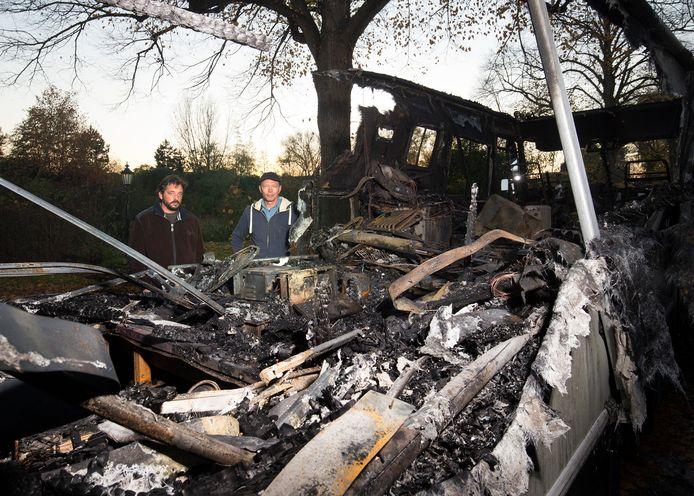 Pim Visser (links) en Jan Ros bij de afgebrande camper.