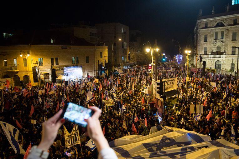 Tienduizenden Israëliërs demonstreren tegen Benjamin Netanyahu. Zij vinden dat hij niet langer premier kan zijn, omdat hij terecht moet staan wegens corruptie. Over drie dagen worden er verkiezingen gehouden, en de partij van Netanyahu doet het goed in de peilingen.  Beeld Getty Images