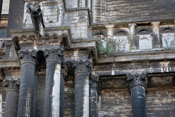 De stenen zijn met roet vervuild, planten groeien tussen de voegen uit en de glas-in-loodramen vertonen beschadigingen.